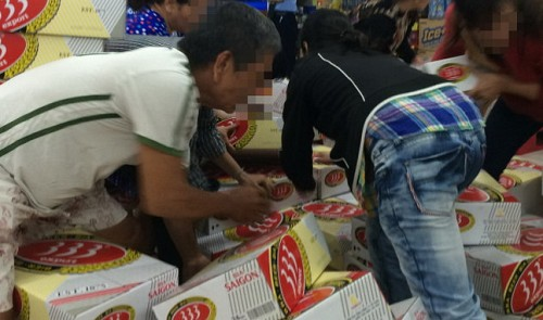 Vietnam. Dealers jostle to buy heavily-discounted beer in Ho Chi Minh City supermarket