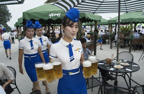 This photo taken on August 12, 2016 shows a waitress carrying jugs of beer to guests before the opening of the Pyongyang Taedonggang Beer Festival on the banks of the Taedong river in Pyongyang. / AFP / Kim Won-Jin        (Photo credit should read KIM WON-JIN/AFP/Getty Images)