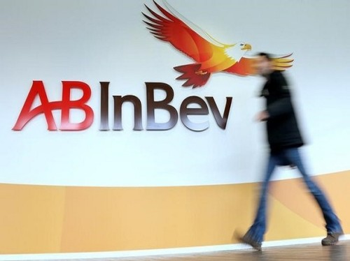 A man walks past the logo of Anheuser-Busch InBev at the brewer's headquarters in Leuven, Belgium February 26, 2014. REUTERS/Francois Lenoir/File photo